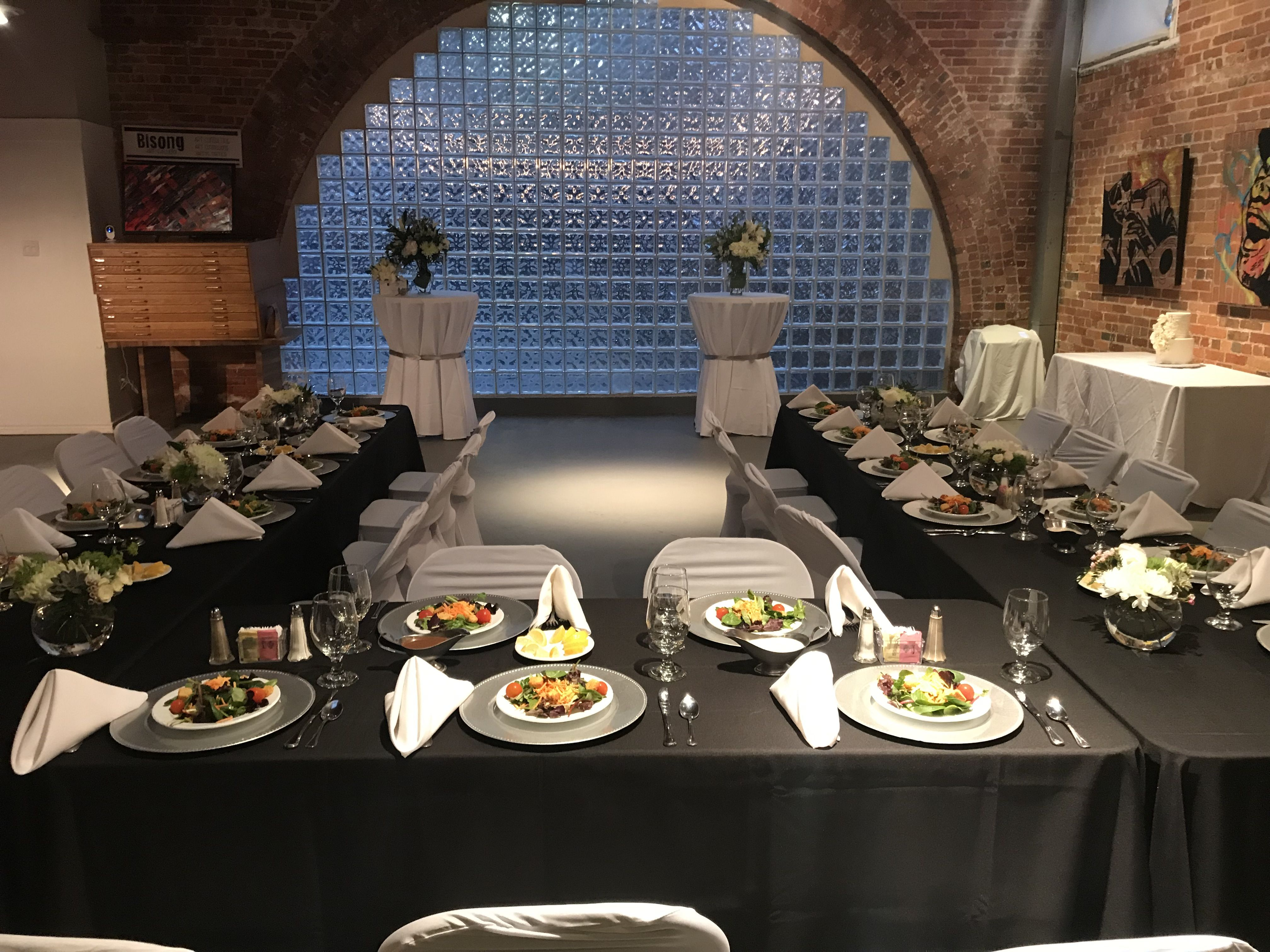 A Small Wedding Reception with preset salads and chargers in black and white by Catering By Norris